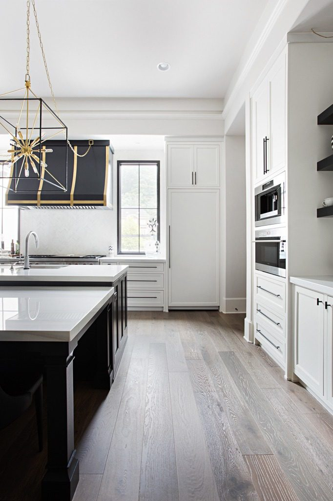 Black white and gold kitchen featuring custom wide plank hardwood flooring by Textures Nashville