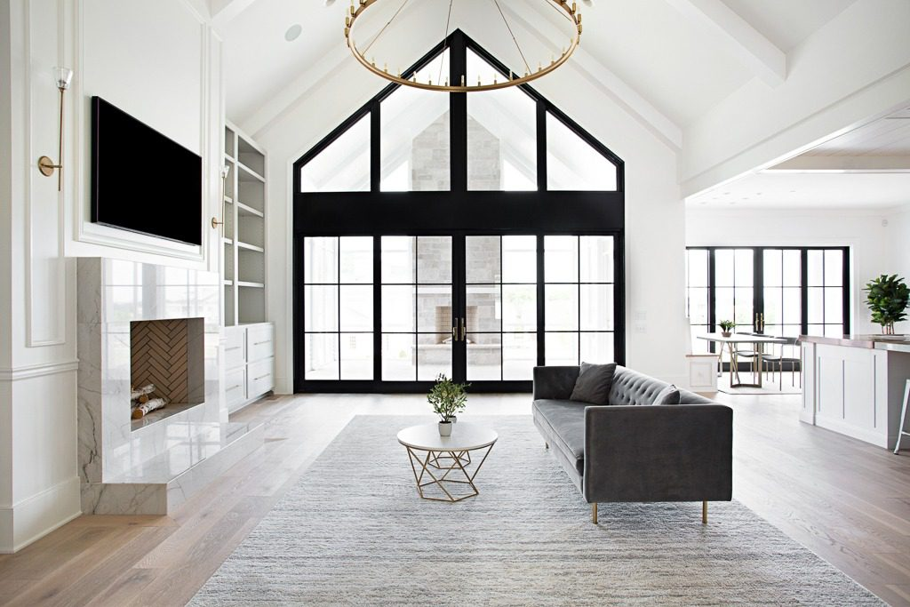 Modern Farmhouse living room featuring large black framed windows and matte finish wide plank hardwood flooring by Textures Nashville