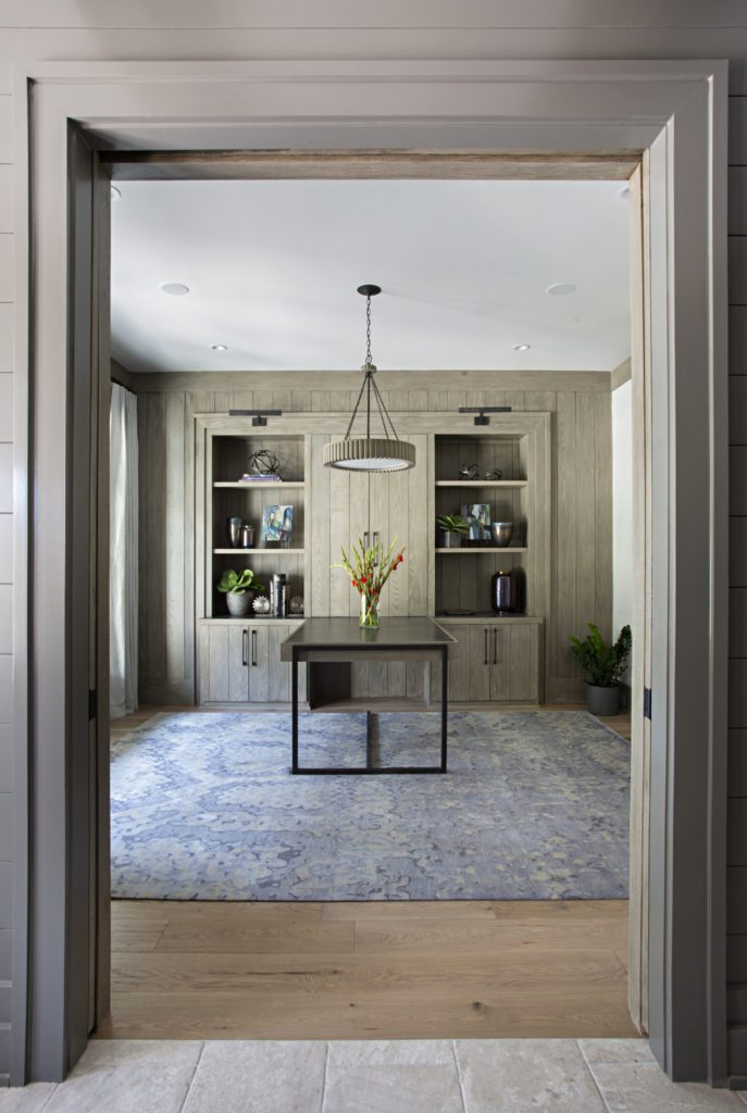 Dining area with builtin bookcases featuring wide plank hardwood flooring by Textures Nashville.